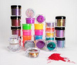 assortment of small vials and jars of nail powder
