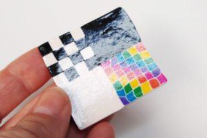 Shiny spray gloss varnish on Premo polymer clay test tile.